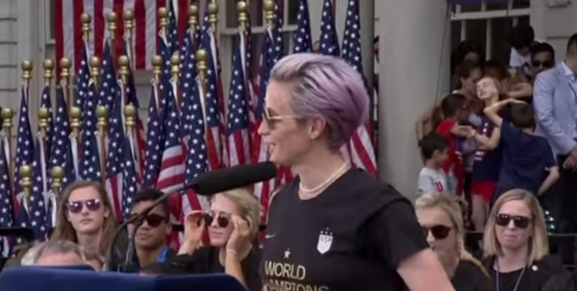 Megan Rapinoe on the podium in front of city hall during the parade of champions