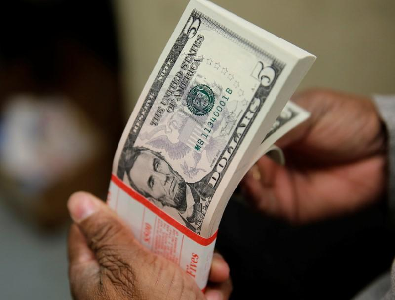 Dollar hovers near two-week low after U.S. yields slip